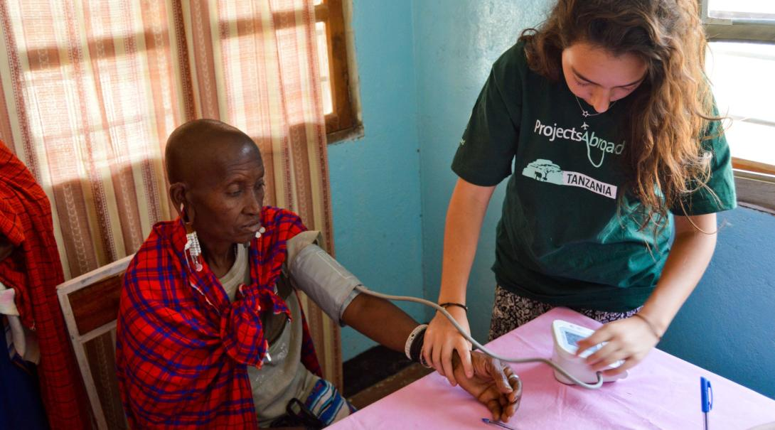 A female Public Health intern measures a patient's blood pressure levels in Tanzania.